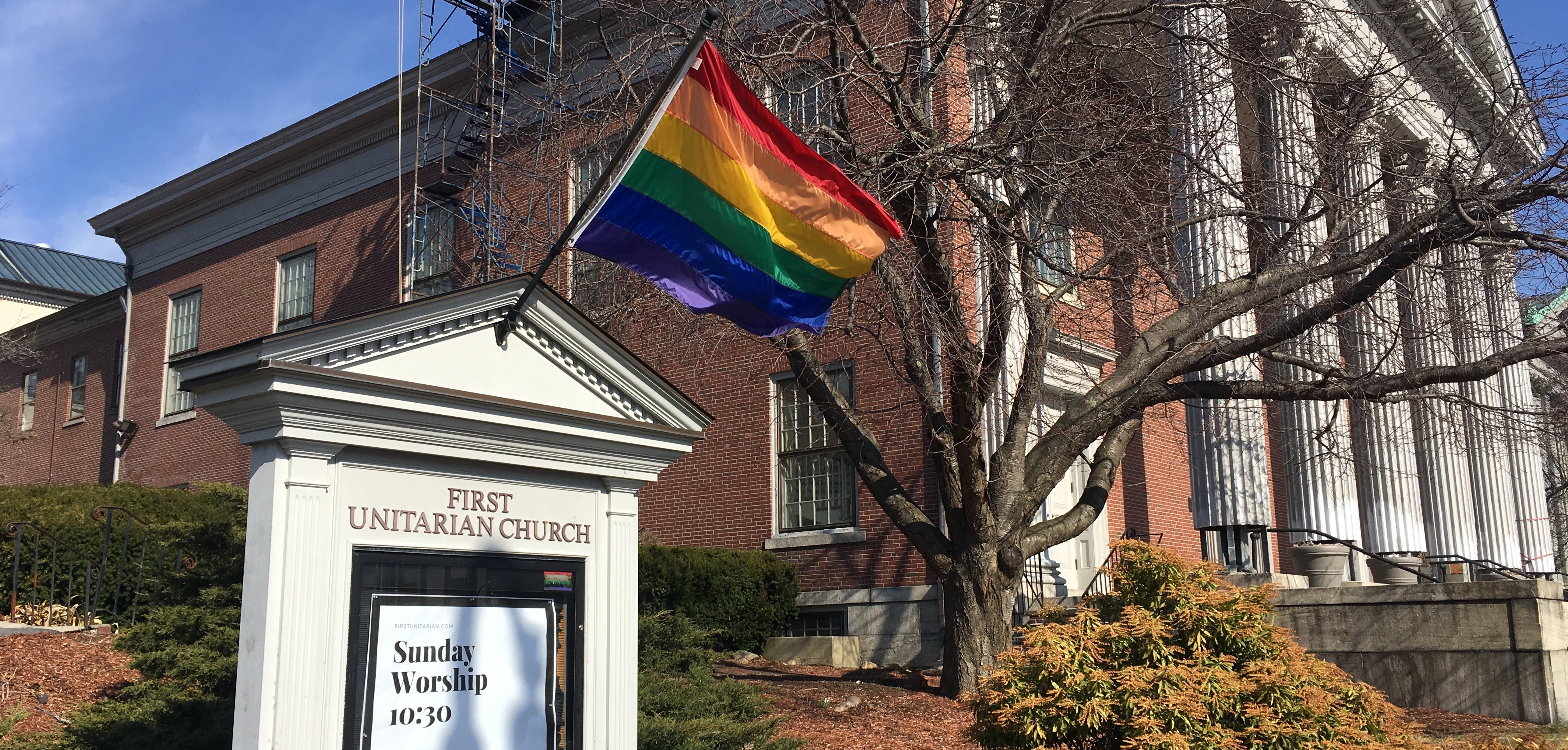 Wayside pulpit with rainbow flag in front of First Unitarian Church